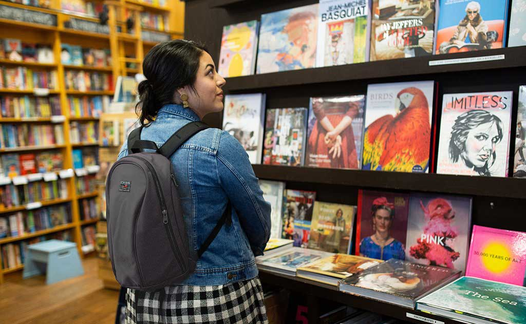 The Luminary 12 backpack in Nebulous worn by a person browsing in a bookstore
