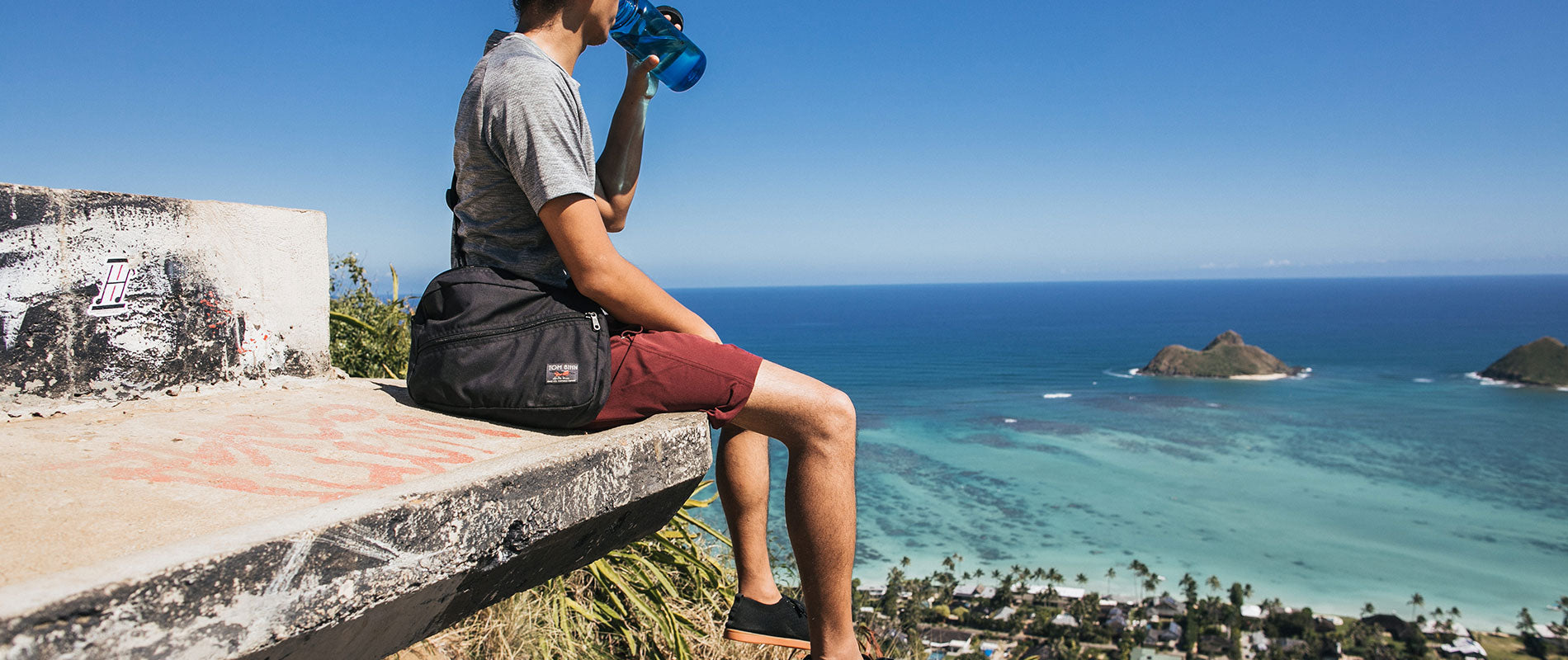Packing Cube Shoulder Bag worn by a man resting after a climb which overlooks the ocean