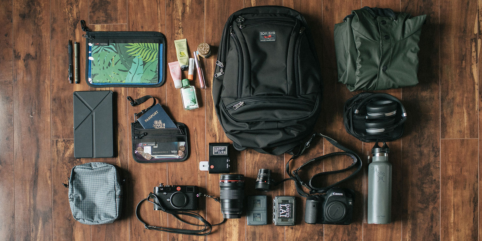 Daily carry items (laptop, jacket, cords, etc.) laid out around a Synapse 19 backpack in Black