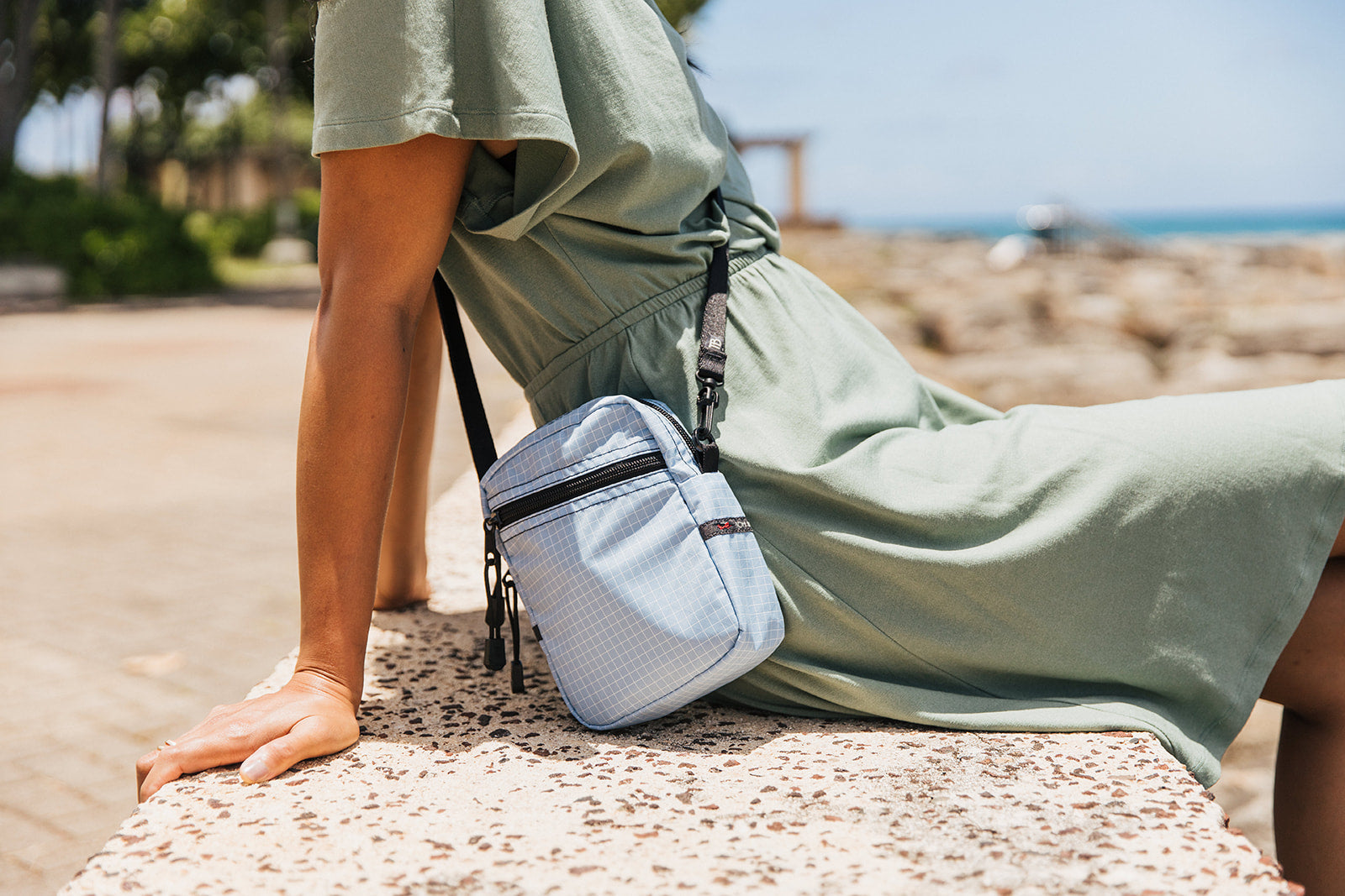 Woman reclining at the beach while wearing a pale green sundress and an Everyday Cubelet in Acuity worn cross-body