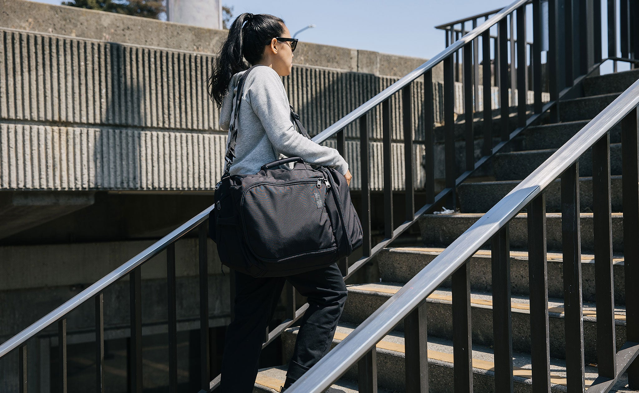 Person carrying the Techonaut as a shoulder bag. They're walking up a flight of stairs outdoors.