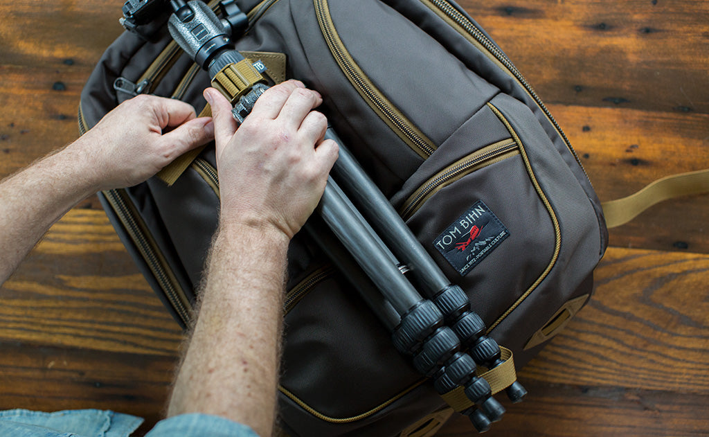 A travel tripod for a DSLR strapped to the outside of the Guide's Edition Synik 30 using the optional Ice Axe loop.