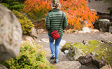 Person wearing a Everyday Cubelet in Mars Red at a Japanese garden. Walking down steps to a pond.