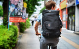 A person wearing the Aeronaut 30 as a backpack while riding a bicycle.
