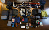 A pack-out for a skiing trip for three people that includes 2 Aeronaut 30s and 1 Aeronaut 45, several packing cubes and accessories (e.g. 3D Organizer Cubes, Spiff Kits) for each, a couple of Yeoman Duffels for photography gear and ski boots, and a set of skis and ski poles.