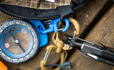 A Small Double Carabiner connecting a compass and a Medium Double Carabiner connecting a pocket knife to the same o-ring in a Handy Little Thing.
