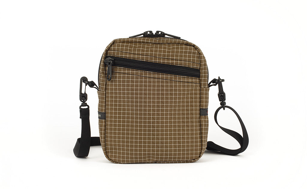An Everyday Cubelet in Coyote Halcyon (brown with a white grid) with a front zipper.