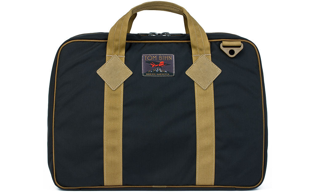 Founder's Briefcase in Black 420 Parapack with Coyote (tan) trim and a logo at the top-middle.