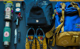 A Guide's Pack loadout photo with the Guide's Pack, a pair of shoes, a jacket and beanie, a pair of water bottles, a compas, a pocket knife and pocket flashlight, and various tools.