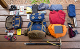 A loadout shot of the Guide's Pack with clothing, an ice axe, a pair of Side Pockets with a water bottle, a med kit, some tools and maps, and a head lamp.