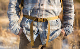 A close shot of a person using the included hip belt of the Guide's Edition Synapse 25.