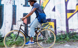 A person wearing the Medium Cafe Bag as a crossbody while riding a bike.