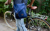 A person wearing the Medium Cafe Bag as a crossbody while walking a bike.