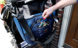 A person retrieving keys from a Parental Unit hung to a stroller using the Stroller/Wheelchair Strap.