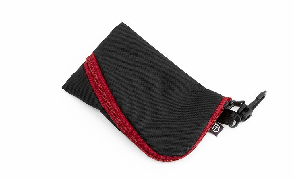 A Mini Ghost Whale Pouch made with black material and an Iberian (red) zipper.