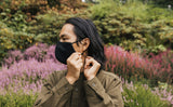 Person adjusting the adjustable ear loops on the V2 Mask in Black Flannel.