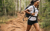 Woman jogging down a hiking trail wearing the Shadow Guide 33 with the sternum and waist belts fastened.