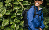 Woman wearing a blue raincoat and smiling while wearing the Shadow Guide 33 on a hike in Hawaii.