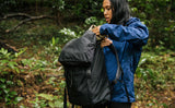 Woman wearing a blue raincoat pulling a hat out of the top pocket of the Shadow Guide; you can see rain drops beading off the fabric of the backpack.