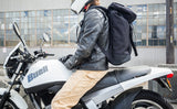 Nik on his Buell Blast motorcycle, helmet and leather jacket on, wearing the Shadow Guide 33 backpack.