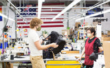 Nik holding a prototype of the Shadow Guide 33 backpack in our Seattle factory. He is talking with Fong and both are wearing masks. Rainbow, U.S.A. and Earth flags are in the background.