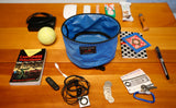 A Large Travel Tray surrounded by various accoutrements: a Cantonese Phrasebook, a USB keydrive, a charging battery, a dongle, a pair of earbuds and MP3 player, a bit of change, a carabiner and key, a Metrocard, a pen, a notepad, a tube of lotion, some snacks, and a tennis ball.