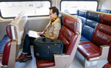 A person using a laptop while sitting in a rail car seat with a Black 525 Ballistic Western Flyer in the seat beside them.