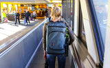 Another perspective of the woman wearing the Aeronaut 30 on the moving sidewalk at the airport photographed from behind.