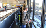 A woman wearing the Aeronaut 30 as a backpack on a moving sidewalk at an airport with a tripod lashed to the side.
