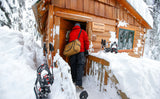 Arriving at a snowy cabin with the Aeronaut 30 carried via the Absolute Shoulder strap.