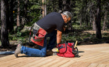 A person repairing a wooden the deck with The Truck filled with tools.