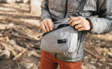 Person wearing the Design Lab Edition Packing Cube Shoulder Bag in Northwest Sky while standing in a forest. They are opening the front zipper pocket.
