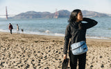 Person wearing the Design Lab Edition Packing Cube Shoulder Bag in Acuity blue while standing on a beach in San Francisco.