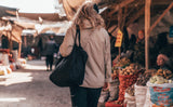 A person walking in a market with the Large Zip-Top Shop Bag.