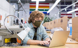 Person wearing V2 mask and working at a laptop.