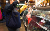 A person putting a sealed bag of popped popcorn in the main compartment of the Pop Tote.