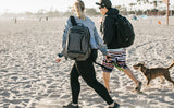 Two people walking a dog at the beach wearing Synik 22s