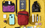 Photo with items around an Everyday Cubelet that might fit inside: passport, phone, make-up, earbuds, headlamp, eye mask.