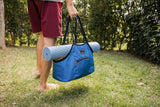 Person carrying the Truckasana yoga tote with a yoga mat cradled in it. They are outdoors on green gass.