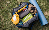 The Truckasana tote bag opened to show Stuff Sacks in both end compartments and a yoga block and water bottle in the middle.