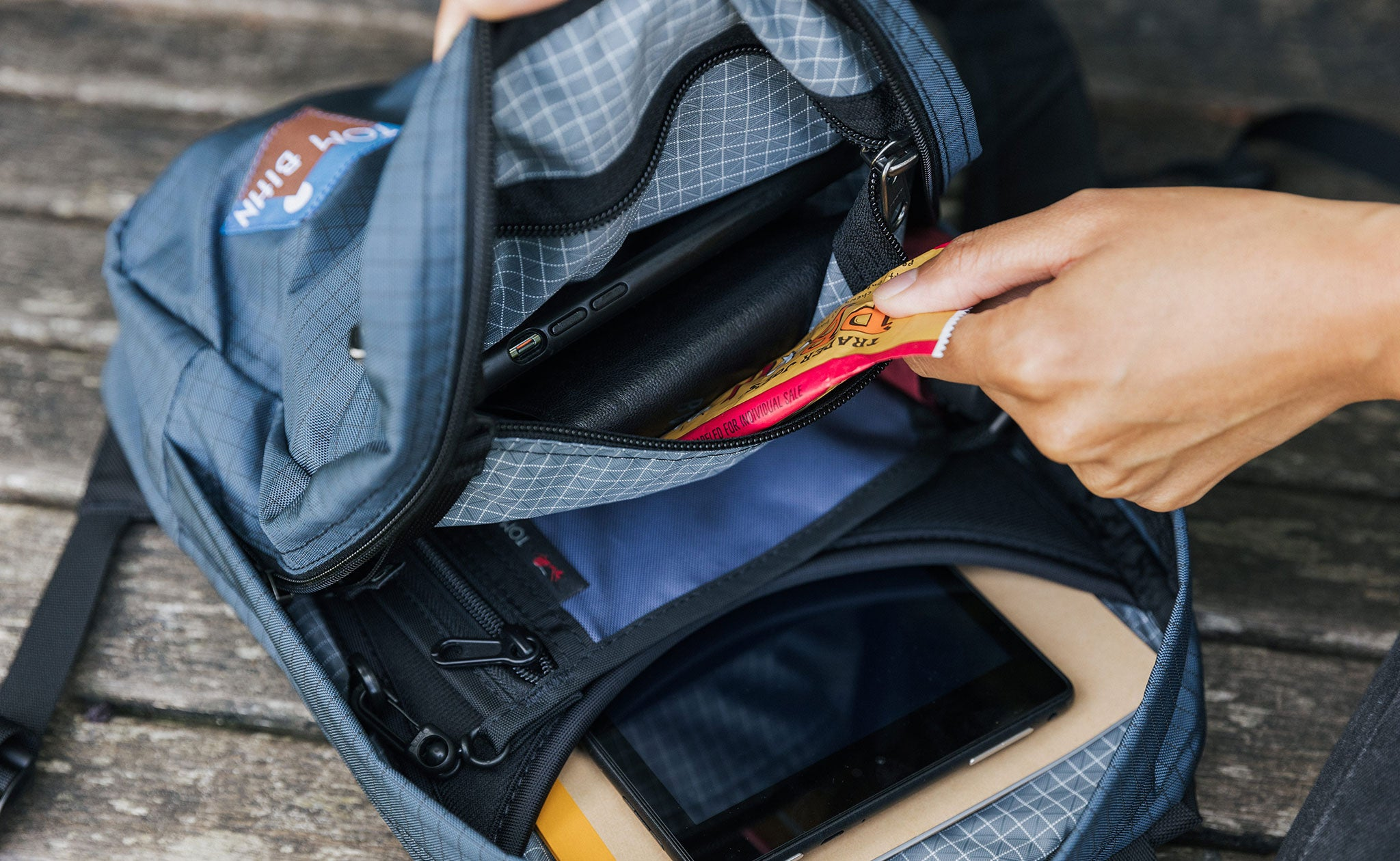 A person removing a protein bar from the interior pocket of the Zeitgeist (also filled with a wallet and cellphone)