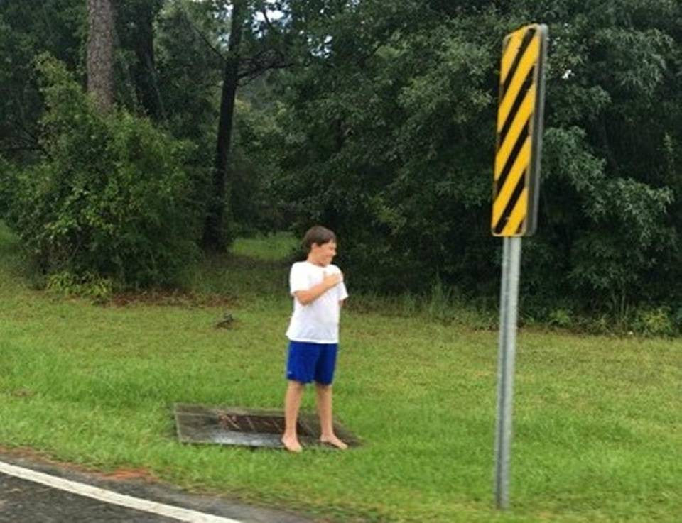 LITTLE BOY STANDS IN RAIN TO SALUTE WWII VET FUNERAL PROCESSION