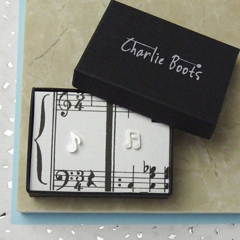 Silverplated music note stud earrings on an illustrated  background