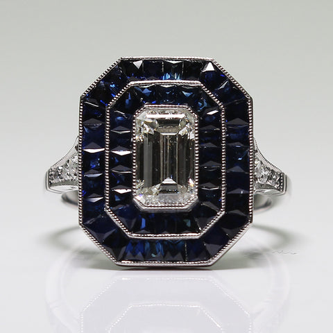 1 Emerald Cut Diamond  = 1.00ct and Round Diamonds  = .15ctw Sapphires = 2.50ctw  6.1gr All Weights Approx Platinum Ring LR3887