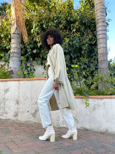 "Mecca wears <a href=""https://shainamote.com/collections/new-arrivals/products/the-trench-in-pale-khaki?variant=32562913083466"" target=""_blank"">The Trench in Pale Khaki</a>"