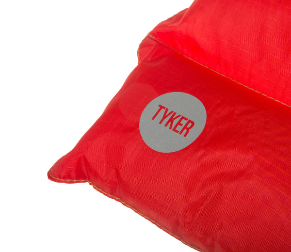 close up of reflective tyker logo on a red dog bed