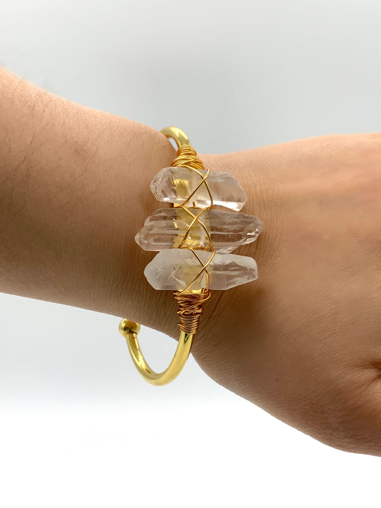 Triple clear quartz wire wrapped to gold adjustable bangle, displayed on wrist