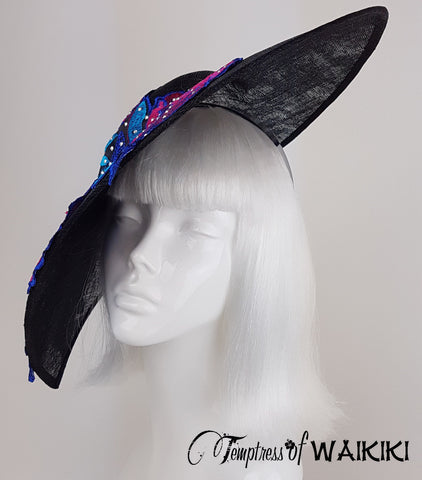 A unique, wide brimmed, one of a kind black sinamay hat, with a beautiful pink and blue appliqué sprinkled in sparkles.
