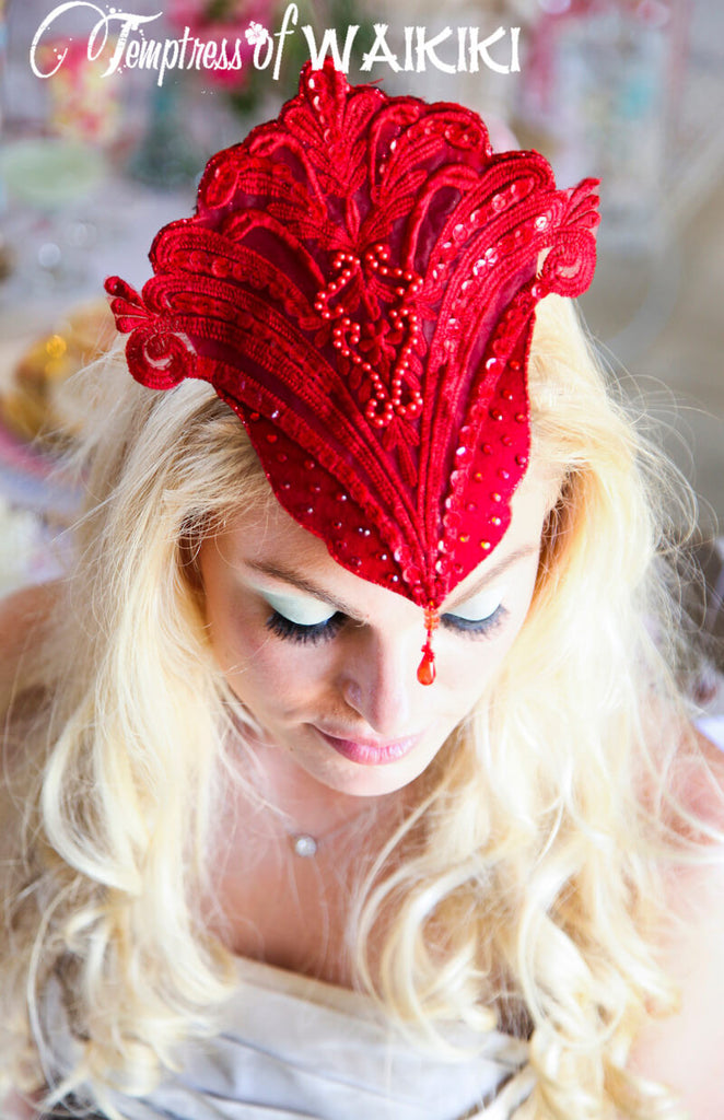 Red mini lace headdress fascinator decorated in red lace, beads, crystals, glitter and features a red jewel dripping off the central point. Lightweight and hand blocked to fit your head. Attaches with a comb and adjustable hat elastic.