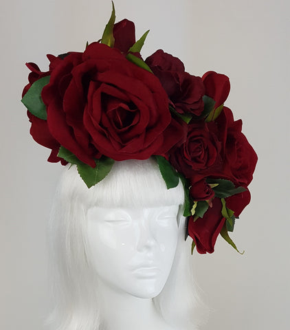 Opulent giant red rose headdress, one of a kind! Many red velvet roses and leaves set on a wired blocked sinamay base. The base is backed with satin and attaches with a comb and hat elastic.  Temptress of Waikiki is well known for producing the most fabulous flower crowns and flower headdresses, most of which are one of kind. This headdress is perfect for Ladies Day at Royal Ascot or a decadent bride or even mother of the bride.